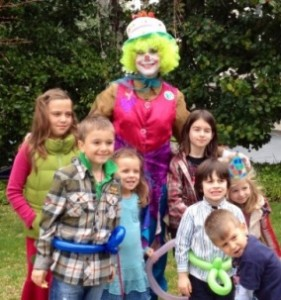 Denise is dressed as Bouncy the Clown and posing with happy kids at an outdoor birthday party.