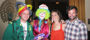 Denise, as Bouncy the Clown, poses with smiling adults at a birthday party in San Francisco.
