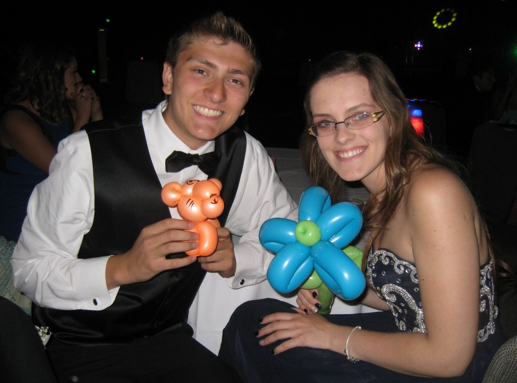 A couple holding balloons twisted into a tiger and a flower during prom night