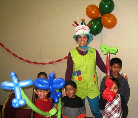Denise the party entertainer with children and their twisted balloons at a party