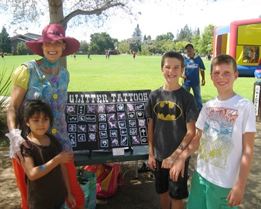 Denise poses with 3 children by her glitter tattoo chart in the park.