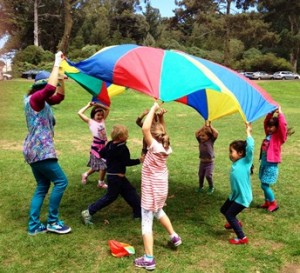 Denise playing parachute games with a group of children in the park
