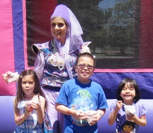 Denise as the Magical Genie, with 3 happy kids, at a children's party. Bouncy castle on the background.