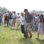people playing a 3-legged race, with a crowd watching
