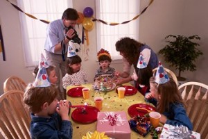 A father videotapes his son's birthday party as the mother brings the cake to the table.