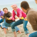 a group of people playing tug of war with a yellow rope on the beach