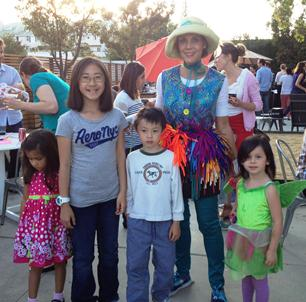 Denise posing with 4 children at a company picnic