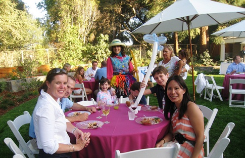 Denise posing with a table of guests at a company picnic