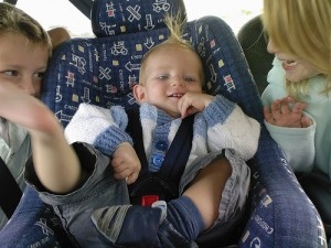 a baby sitting on a car seat in between 2 other children
