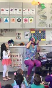 Children's entertainer Denise blows confetti during her Magic Comedy Show at a preschool birthday party.