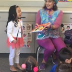Children's entertainer Denise holds a book during her Magic Comedy Show at a preschool birthday party.