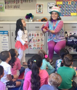A girl is curious about what Denise is holding during her Magic Comedy Show at a preschool birthday party.