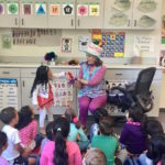 Children's entertainer Denise asks a girl to help during her Magic Comedy Show at a preschool birthday party.