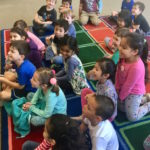Children look intently during Denise's Magic Comedy Show at a preschool birthday party.