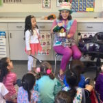 Children's entertainer Denise opens the magic pan during her Magic Comedy Show at a preschool birthday party.