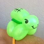 a green balloon twisted into the shape of a turtle, attached to a bracelet